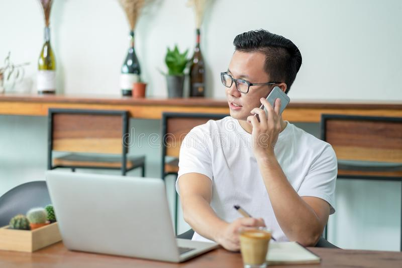 Przypadkowy azjatykci mężczyzna opowiada na telefonie komórkowym pracuje z laptopu com fotografia stock