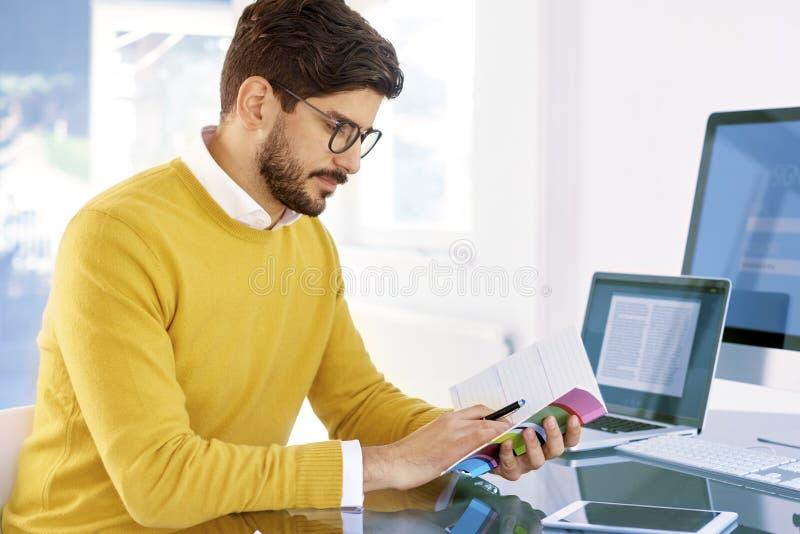 Przypadkowy biznesmen trzyma dzienniczek w jego ręce podczas gdy siedzący wewnątrz zdjęcie royalty free