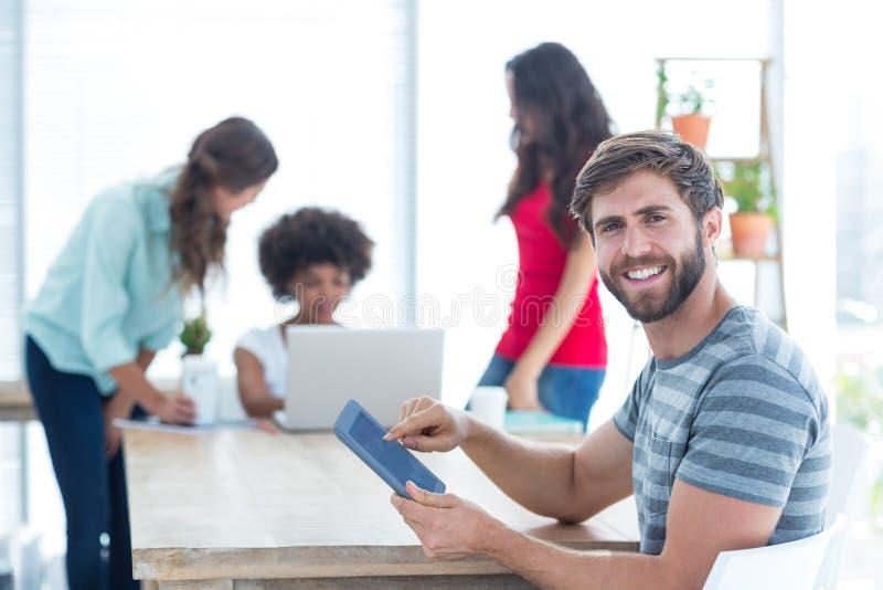 Przypadkowy biznesmen używa cyfrową pastylkę z kolegami behind w biurze zdjęcia stock