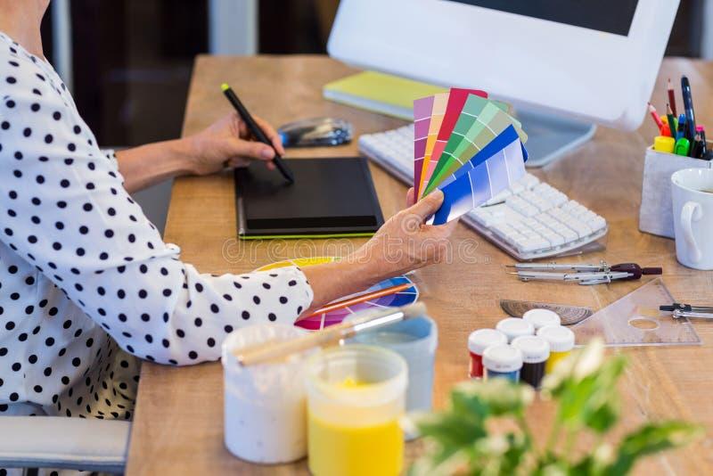 Przypadkowy bizneswoman patrzeje colour rysunek z digitizer i swatch zdjęcie stock