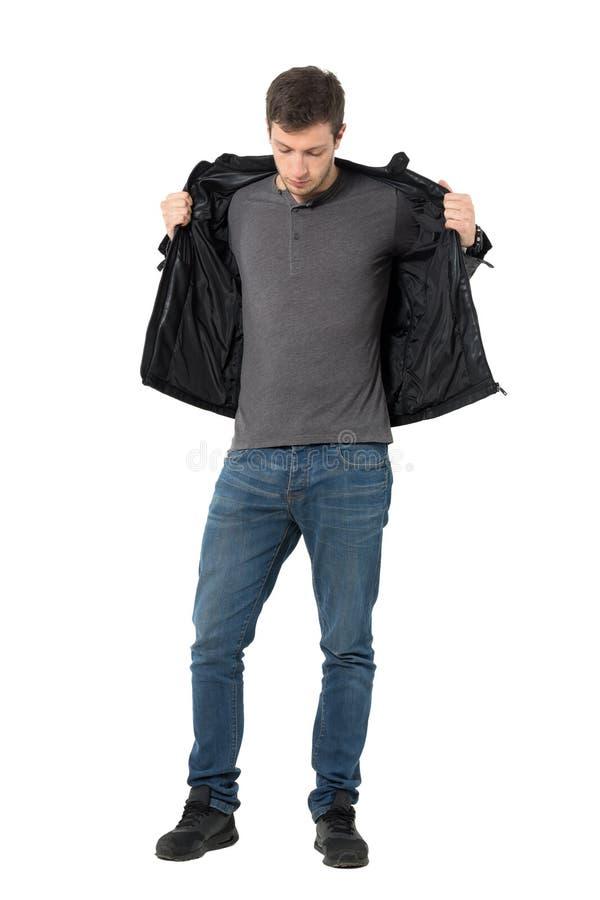 Przypadkowy mężczyzna patrzeje w dół w cajgach bierze daleko skórzaną kurtkę fotografia royalty free