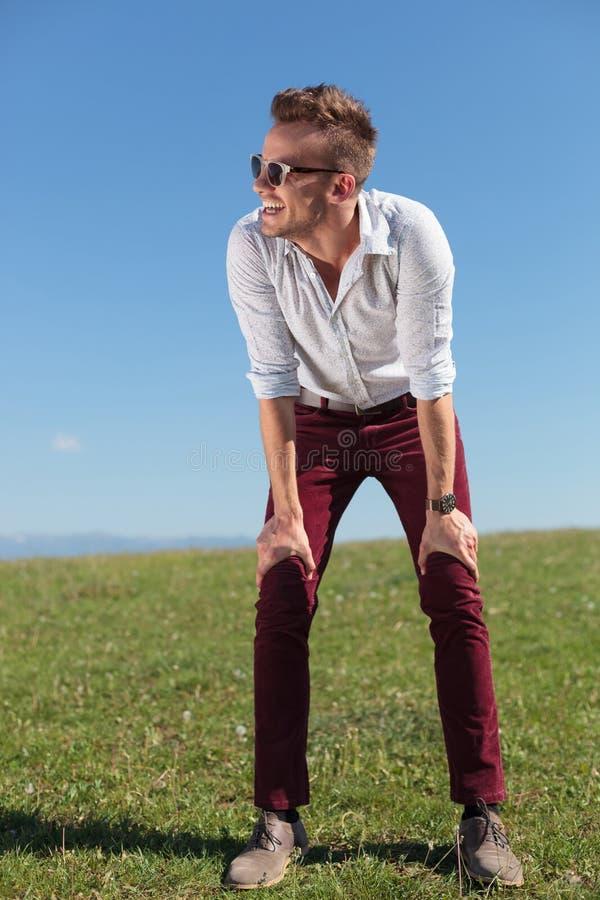 Przypadkowy mężczyzna stoi plenerowego z rękami na kolanach zdjęcie royalty free