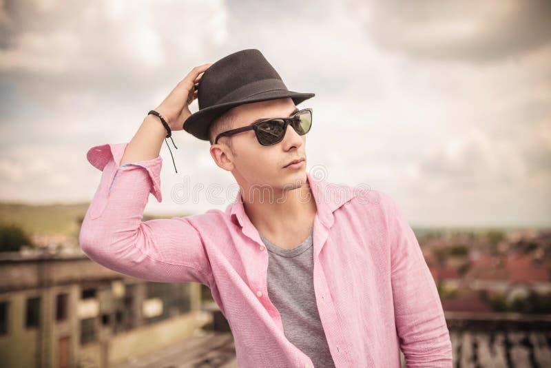 Przypadkowy mężczyzna załatwia jego kapelusz na głowie z okularami przeciwsłonecznymi zdjęcie stock