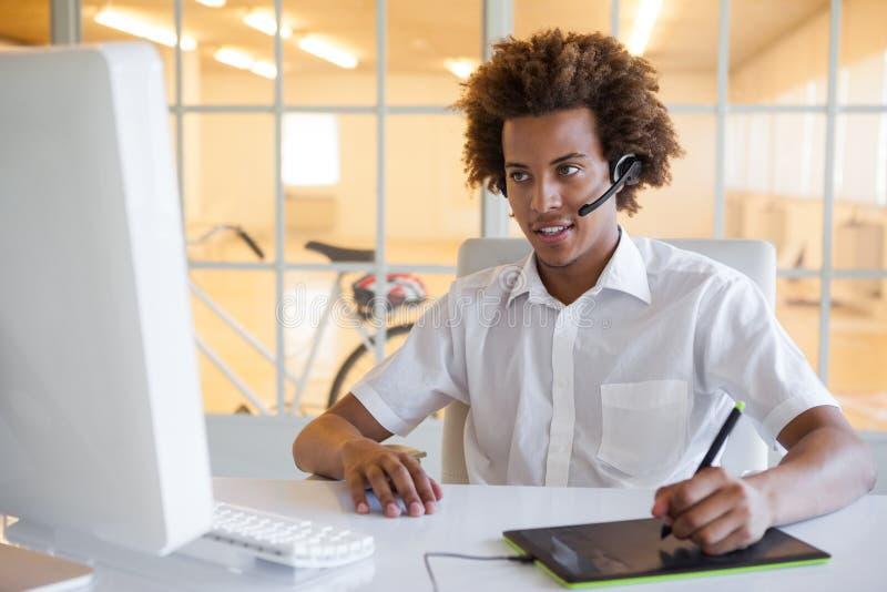 Przypadkowy młody biznesmen używa digitizer i słuchawki przy biurkiem zdjęcie royalty free