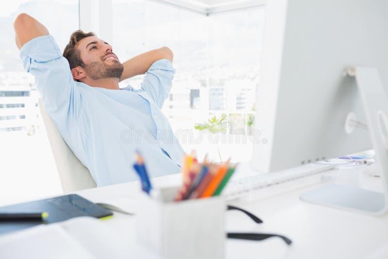 Przypadkowy młody człowiek odpoczywa z rękami za głową w biurze zdjęcia stock