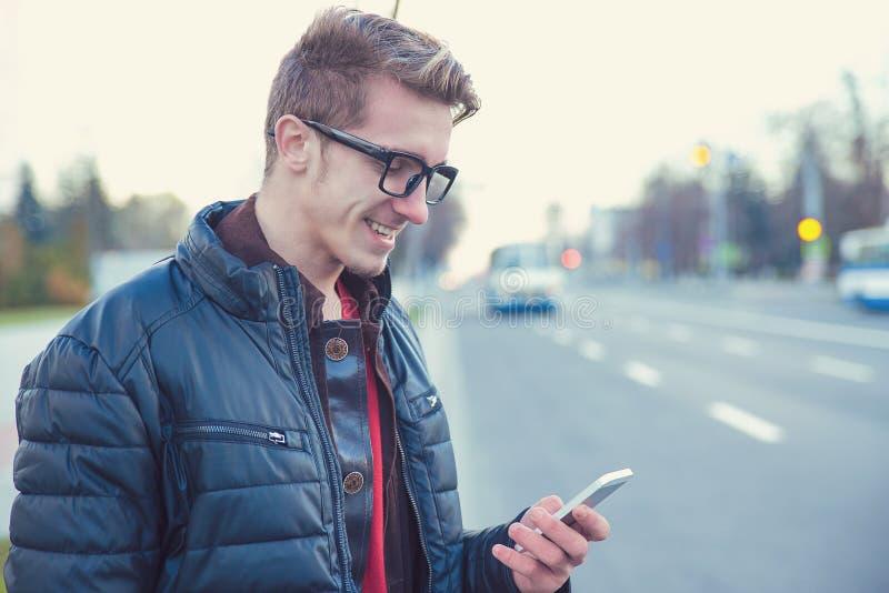 Przypadkowy młody człowiek używa telefon na ulicie obraz stock