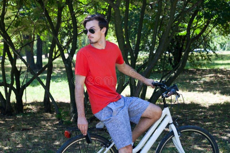 Przypadkowy młody człowiek z okularami przeciwsłonecznymi na roweru odpoczywać obraz royalty free