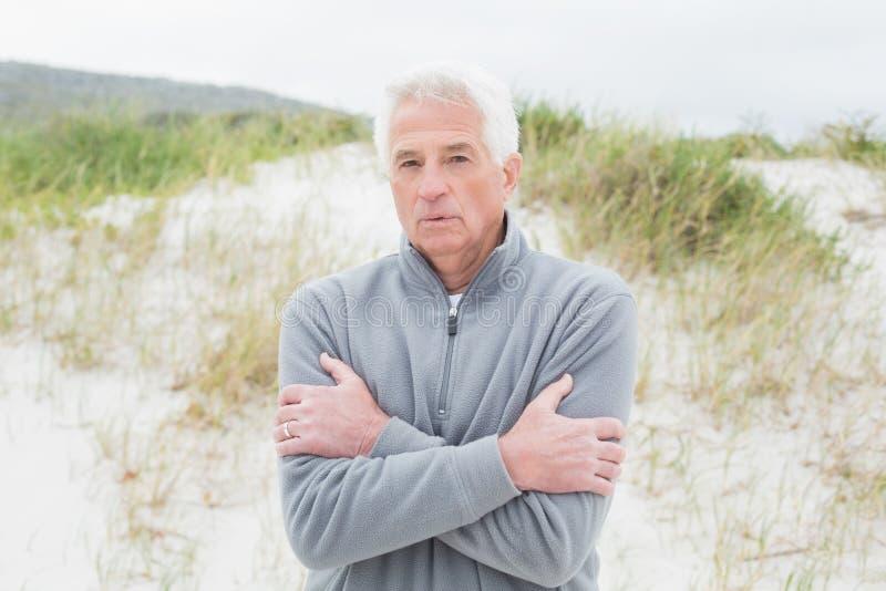 Przypadkowy starszego mężczyzna czuciowy zimno przy plażą obrazy stock
