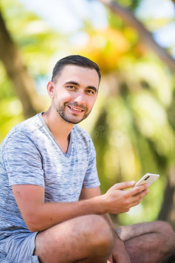 Przypadkowy szczęśliwy mężczyzna pisać na maszynie na smartphone obsiadaniu na ławce w parku fotografia royalty free