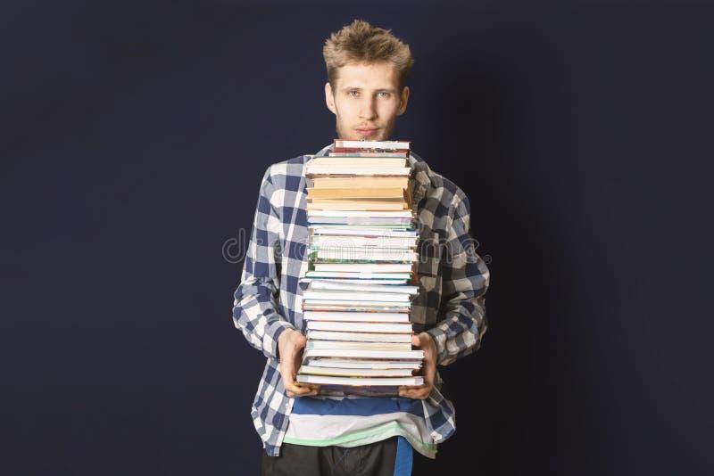 Przypadkowy uczeń niesie ogromną stertę książki na ciemnym tle f fotografia royalty free