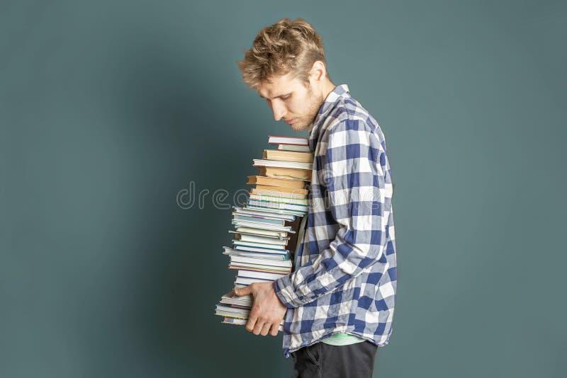 Przypadkowy uczeń niesie ogromną stertę książki na ciemnym tle f zdjęcia stock