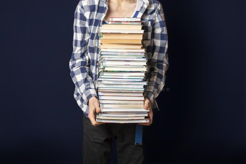 Przypadkowy uczeń niesie ogromną stertę książki na ciemnym tle f zdjęcie royalty free