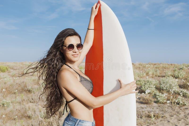 Przyrodni długość portret młody uśmiechnięty modniś dziewczyny mienia surfboard podczas gdy pozujący outdoors w słonecznym dniu obrazy stock