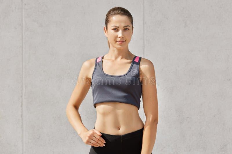 Przyrodni długość strzał ufna młoda sportsmenka schudnięcie doskonalić ciało kształt, jest ubranym sportów ubrania, modela salowy zdjęcie stock