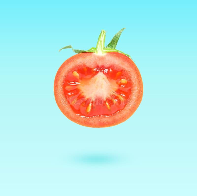 Przyrodni Pomidorowy latanie w powietrzu nad błękitnym tłem, karmowy lewitacji pojęcie fotografia royalty free