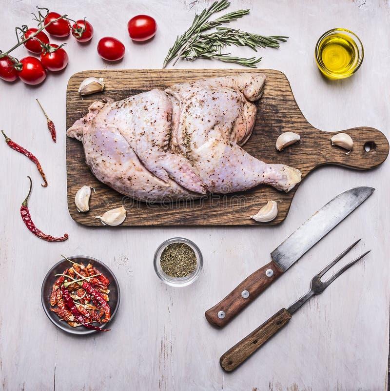 Przyrodni surowy kurczak, składniki dla gotować, pomidory, nóż i rozwidlenie dla mięsa, pieprzymy drewnianego nieociosanego tła o obraz stock