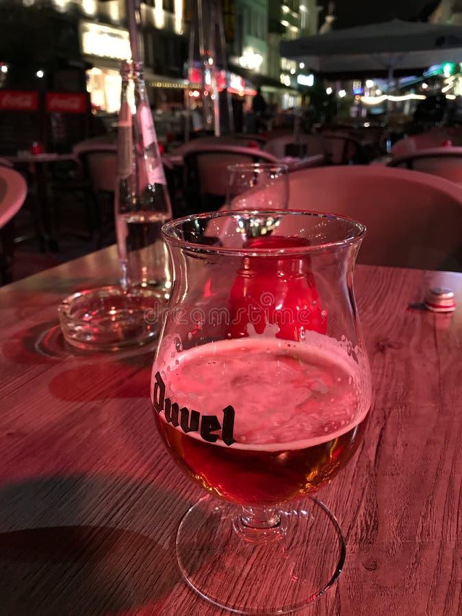 Przyrodni szkło Duvel piwo przy plenerowym stołem kawiarnia w Antwerp, Był zdjęcia royalty free
