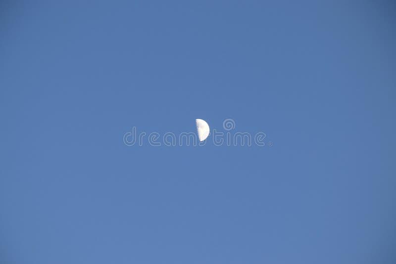 Przyrodnia księżyc na niebieskim niebie w popołudniu w górę Mały miesiąc na monophonic tle z białymi chmurami fotografia stock