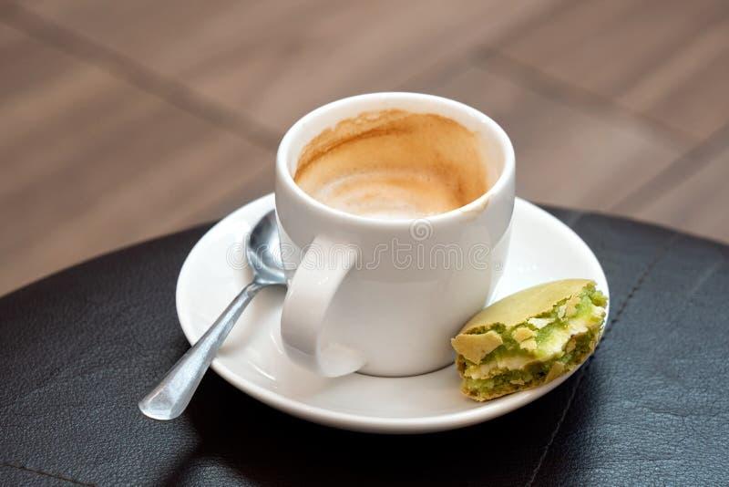 Przyrodnia pełna filiżanka kawy espresso macchiato z metal łyżką i połówka jedzący pistacjowy macaron na spodeczku Czarny skóra s zdjęcie stock