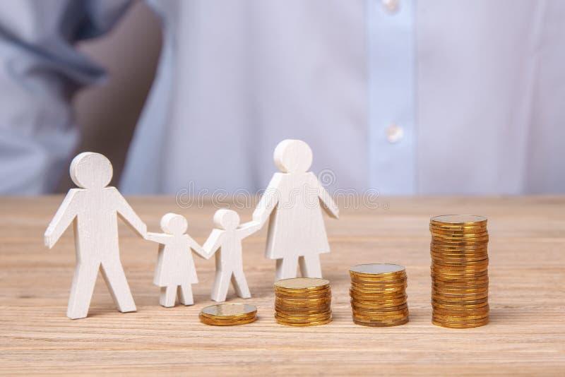 Przyrost rodzinny budżet Mężczyzna trzyma rodziny od ojca, matki, córki i syna jego, przeciw tłu sterta monety zdjęcie stock