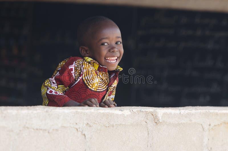 Przystojna Afrykańska chłopiec Śmia się Za ścianą przy szkołą zdjęcie royalty free