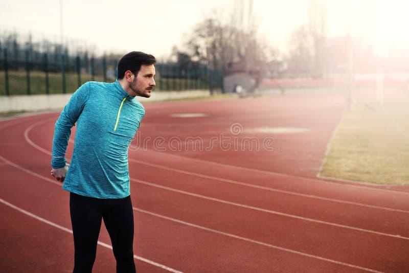 Przystojna atleta rozgrzewkowa up przed biegać obrazy royalty free