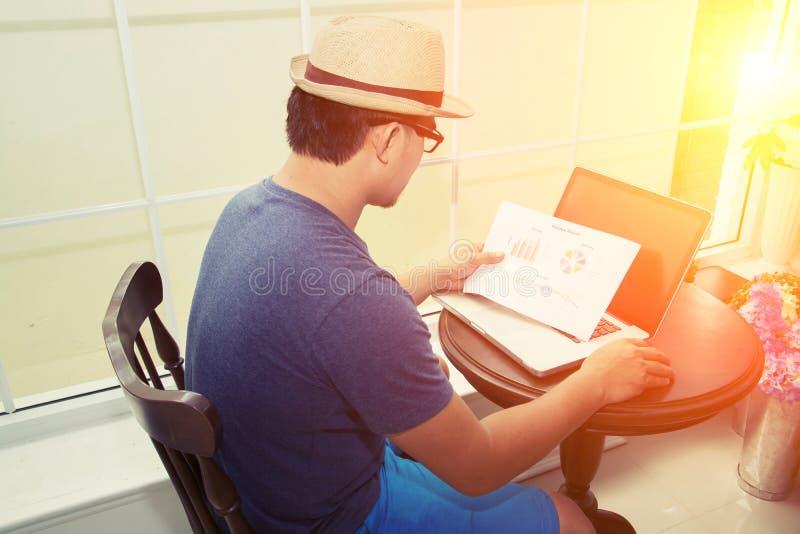 Przystojna biznesmen analiza sporządza mapę z jego laptopu obsiadaniem dalej zdjęcia stock