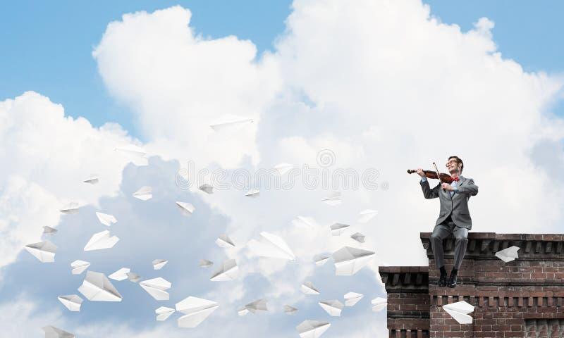 Przystojna biznesmen sztuka jego papierów samoloty i melodia lata wokoło obrazy royalty free