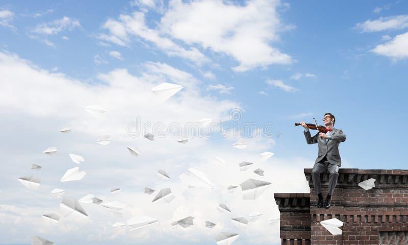 Przystojna biznesmen sztuka jego papierów samoloty i melodia lata wokoło fotografia stock