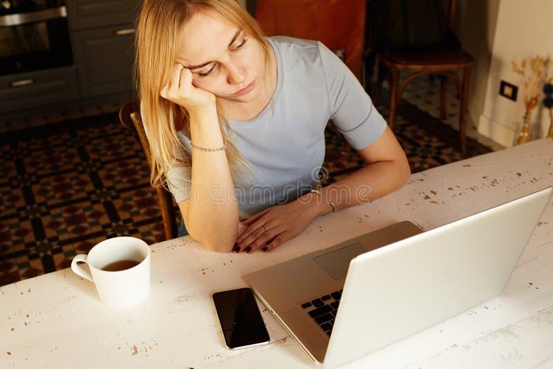 Przystojna blond dziewczyna pracuje w domu na laptopie zdjęcia royalty free