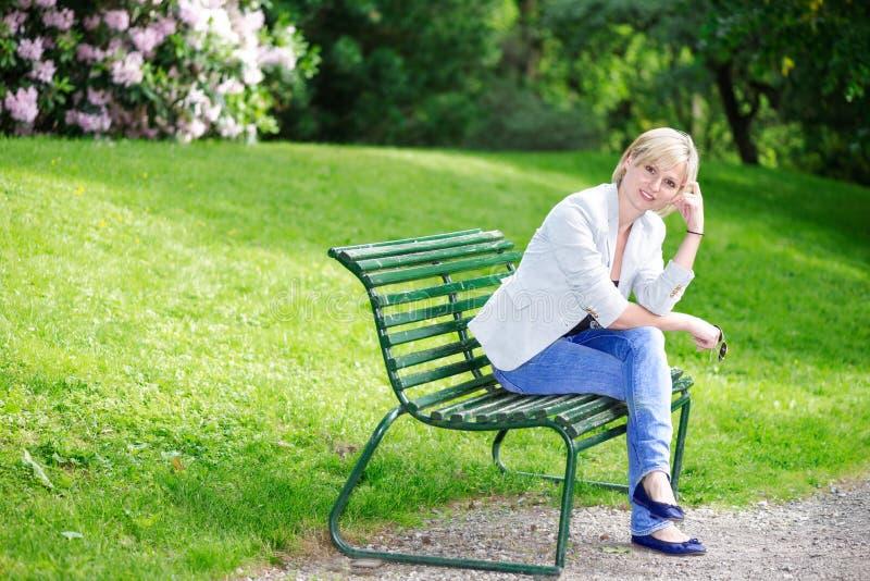 Przystojna blond kobieta patrzeje kamerę na ławce obrazy royalty free