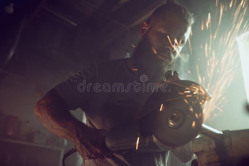 Przystojna brutalna samiec naprawia motocykl w jego garażu pracuje z kółkowym z brodą zobaczył W garażu mnóstwo iskry zdjęcie royalty free