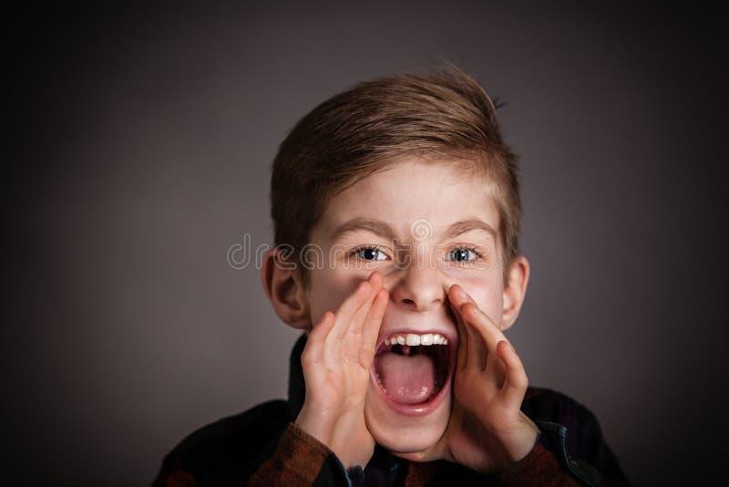 Przystojna chłopiec Krzyczy przy kamerą Przeciw szarość zdjęcie royalty free