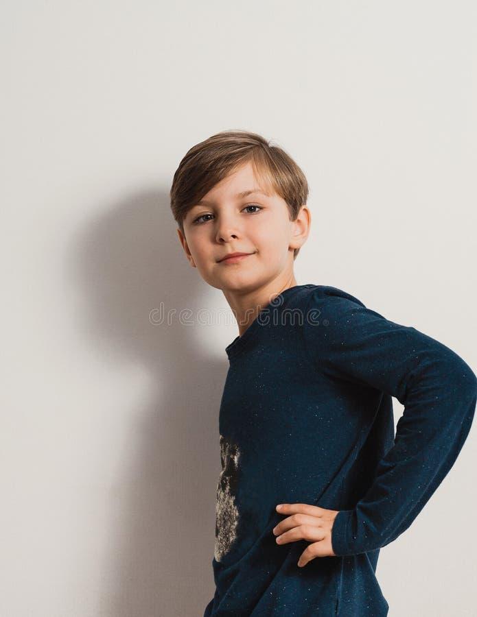 Przystojna chłopiec pozycja białą ścianą, ono uśmiecha się zdjęcia stock