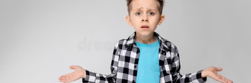 Przystojna chłopiec w szkockiej kraty koszula, błękitnej koszula i cajgów stojakach na szarym tle, Chłopiec rozprzestrzenia jego  fotografia royalty free