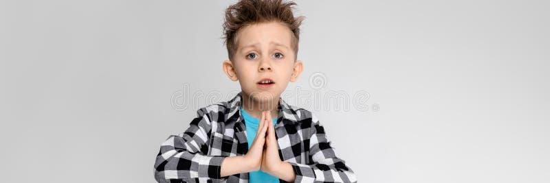 Przystojna chłopiec w szkockiej kraty koszula, błękitnej koszula i cajgów stojakach na szarym tle, Chłopiec składał jego ręki nad zdjęcie stock