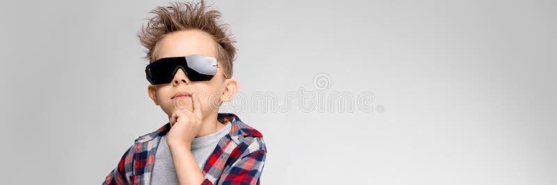 Przystojna chłopiec w szkockiej kraty koszula, szarej koszula i cajgów stojakach na szarym tle, Chłopiec w czarnych okularach prz zdjęcie royalty free