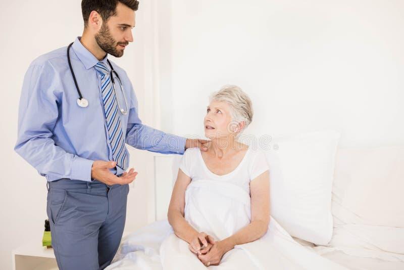 Przystojna domowa pielęgniarka opowiada starsza kobieta obrazy stock