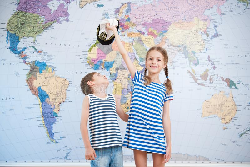 Przystojna dziewczyna w pasiastej żeglarz koszula, chłopiec bawić się na światowej mapy tle i zdjęcia royalty free