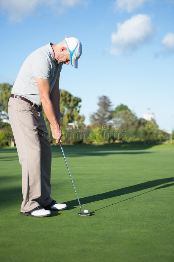 Przystojna golfisty kładzenia piłka na zieleni zdjęcia stock