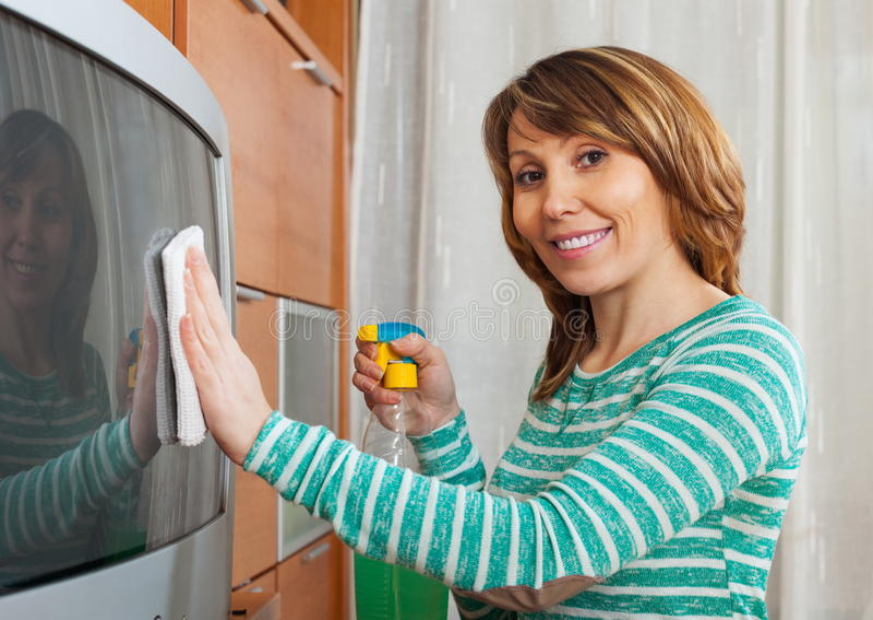Przystojna kobieta czyści TV obrazy stock