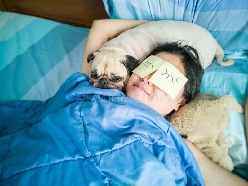 Przystojna kobieta odpoczywa odpoczynek z jej mopsa psem i śpi dokucza obraz royalty free