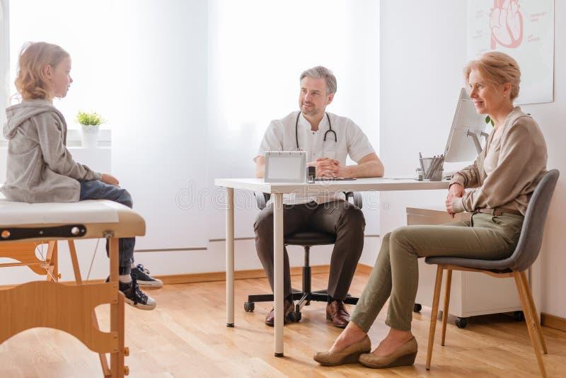 Przystojna lekarka, matka i syn w nowożytnym szpitalnym biurze, obraz stock