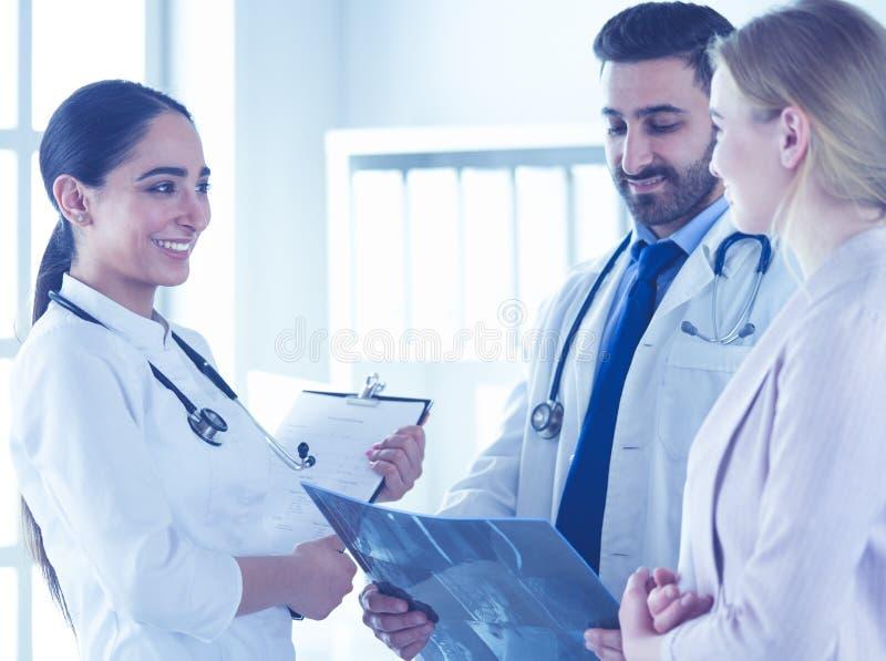 Przystojna lekarka opowiada z m?odym ?e?skim pacjentem i robi notatkom podczas gdy siedz?cy w jego biurze zdjęcia stock