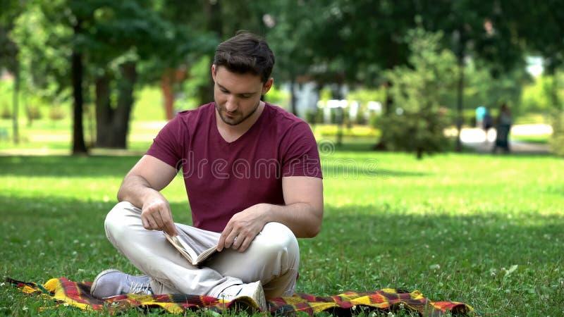 Przystojna męska czytelnicza ciekawa przygody książka, siedzi w parku, bestseller obraz stock