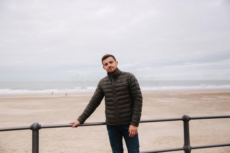 Przystojna mężczyzna pozycja przed morzem północnym Elegancki mężczyzna w khakiej kurtce zdjęcie stock