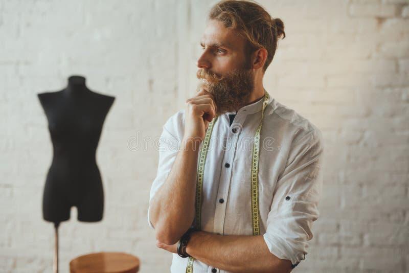 Przystojna męska krawcowa patrzeje zadumany zdjęcie royalty free