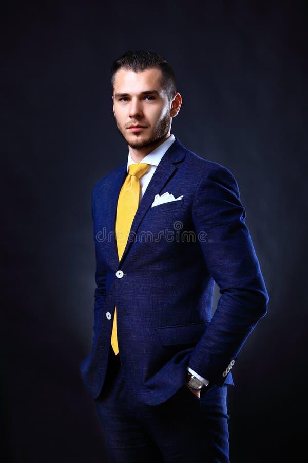Przystojna młoda biznesowego mężczyzna pozycja na czerni fotografia stock