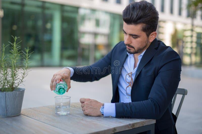 Przystojna młoda biznesowego mężczyzny dolewania woda od butelki w jego szkło zdjęcie stock