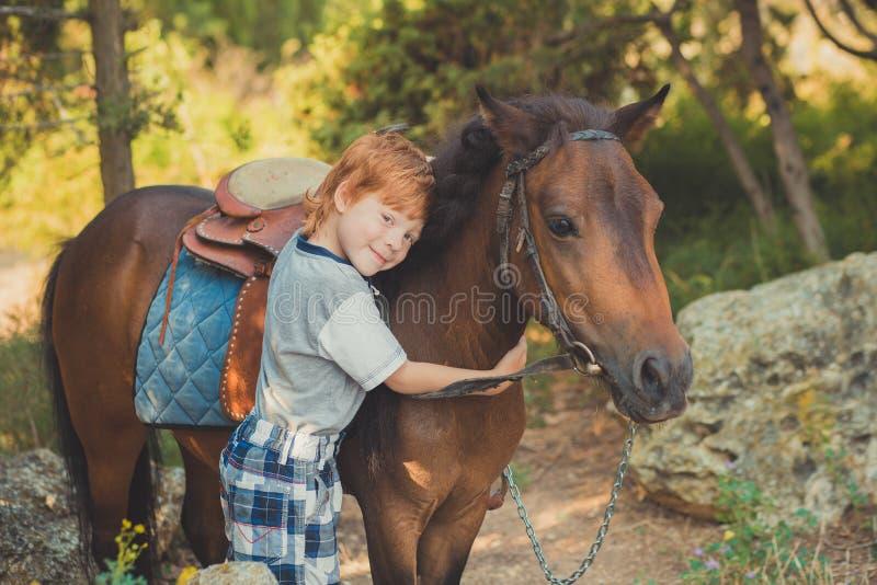 Przystojna Młoda chłopiec z czerwonym włosy i niebieskimi oczami bawić się z jego przyjaciela końskim konikiem w forestHuge miłoś obrazy stock